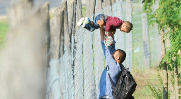 یک پناهجو در حال کمک کردن به فرزندش برای عبور از حصار یک مرکز پذیرش پناهجویان در شهر روسکی در مجارستان – عکس از رویترز