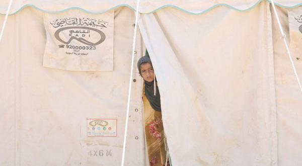 دختری در حال نگریستن از درون خیمه در منطقه ای در استان الجوف در شمال غربی پایتخت که خانواده های آواره به آن جا رفتند – عگس از رویترز