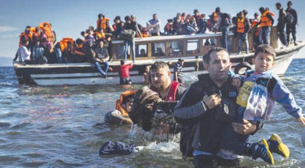 مهاجران سوری و عراقی به هنگام رسیدن به جزیره لیسبوس یونان از سواحل ترکیه با یک قایق – عکس از آسوشیتد پرس