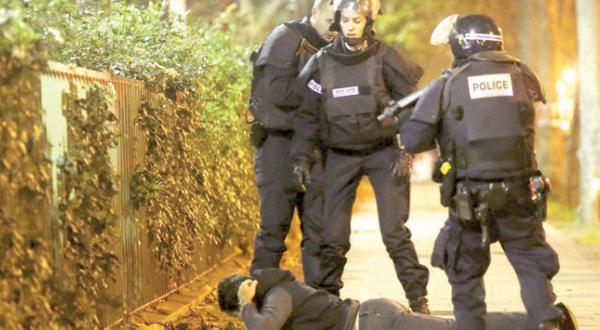افرادی از پلیس فرانسه در حال چک کردن هویت یک جوان پس از حمله تروریستی به سالن کنسرت «باتاکلان» در پاریس – عکس از رویترز