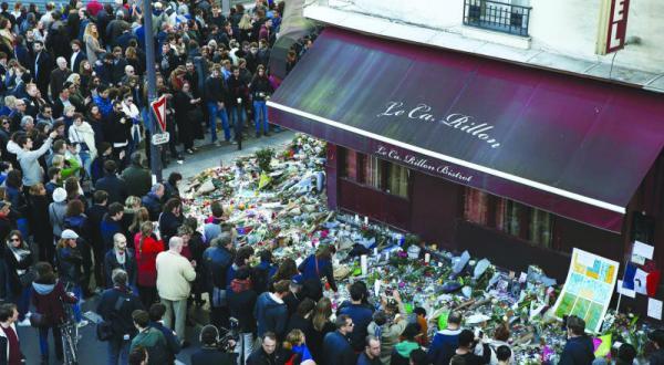 تجمع فرانسویان برای یاد بود قربانیان در مقابل قهوه خانه کاریلیون.. یکی از مکان هایی که مورد هدف حملات تروریستی قرار گرفت – عکس از رویترز