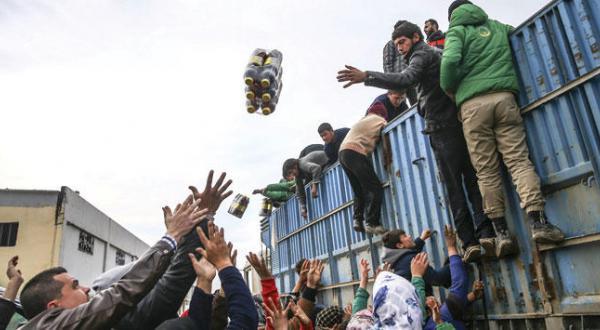 پناهندگان سوری در باب السلام در مرزهای ترکیه در تلاش برای به دست آوردن کمک های غذایی ارائه شده از کمیته های امدادی ترکیه – عکس از گیتی