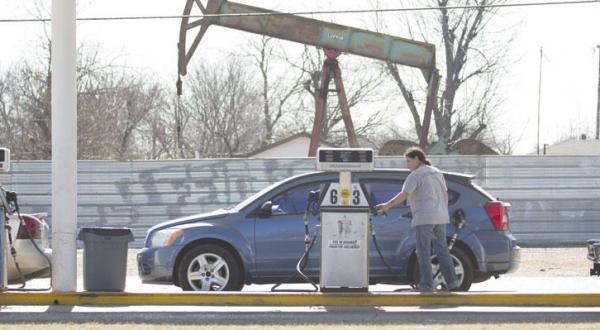 یک زن آمریکایی در حال سوخت گیری خودروی خود در یک ایستگاه گازی در نزدیکی چاه نفتی در شهر اوکلاهاما سیتی در ایالت اوکلاهاما – عکس از خبرگزاری فرانسه