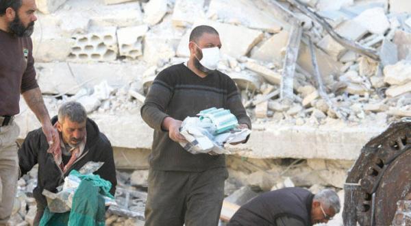 افرادی در حال منتقل کردن تجهیزات پزشکی از زیر آوار بیمارستان «پزشکان بدون مرز» که در بمباران معره النعمان در شمال غرب سوریه آسیب دید – عکس از رویترز