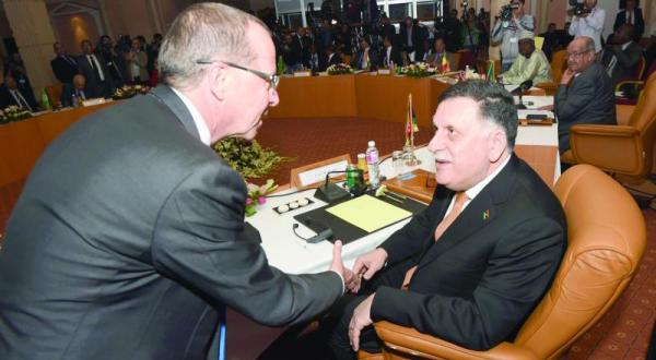 فایز السراج رئیس دولت وحدت ملی لیبی (راست) در حال دست دادن با مارتن کوبلر فرستاده سازمان ملل متحد به لیبی پیش از افتتاح نشست کشورهای هم جوار لیبی در تونس – عکس از خبرگزاری فرانسه