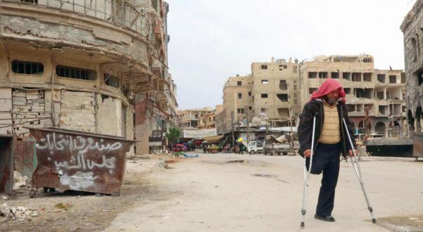 یک مرد سوری که از ناحیه پا مجروح شده در حال عبور کردن از کنار صندوق زباله ای است که روی آن نوشته شده «صندوق انتخابات پارلمان» - عکس از خبرگزاری فرانسه