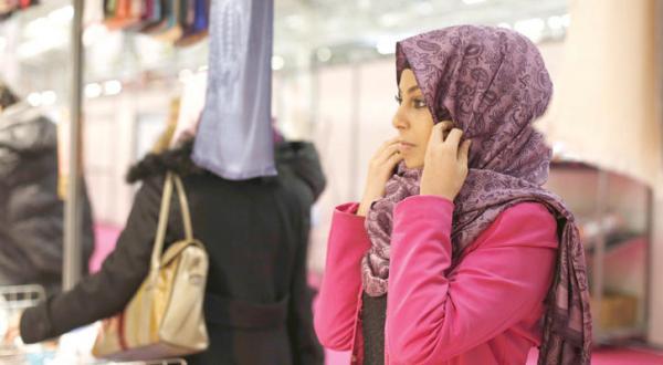 یک دختر جوان در حال امتحان کردن شالی در بخش کنفرانس سالانه اسلامی در نزدیکی پاریس است – عکس از گیتی
