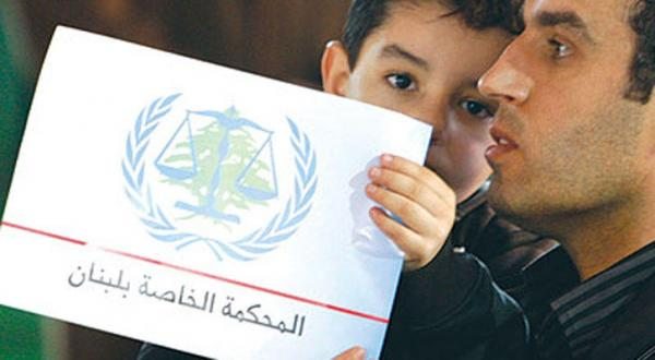 یک لبنانی در حالی که فرزند خود را بغل کرده است شعار دادگاه بین المللی ویژه لبنان را به دست دارد – عکس از رویترز
