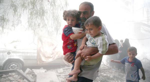 یک سوری در حال انتقال کودکانش از دوما به مکانی امن در پی بمباران توسط جنگنده های نظامی – عکس از رویترز