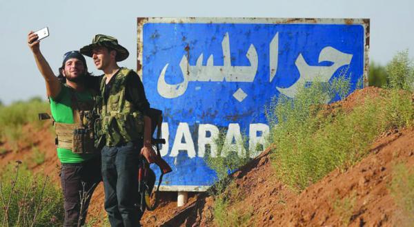مبارزانی از ارتش آزاد سوریه در حال گرفتن عکس سلفی در نزدیکی روستای العمارنه در حومه جرابلس پس از باز پس گیری آن از نیروهای سوریه دموکرات – عکس از گتی ایمجز