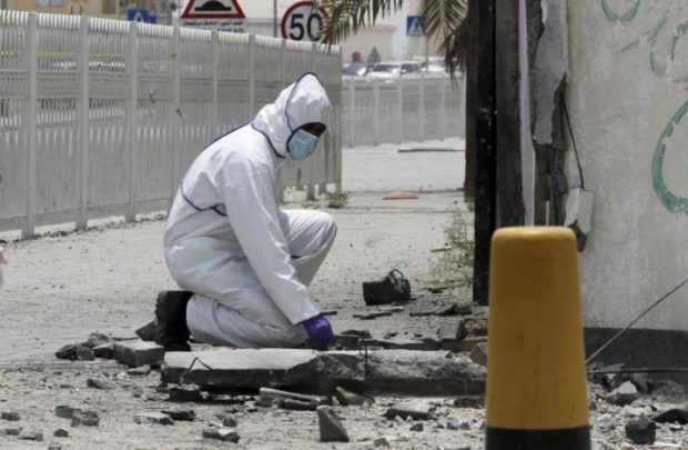An explosives specialist police officer conducts an investigation after a bomb blast in the village of Sitra, south of Manama, Bahrain, July 28, 2015. REUTERS/Hamad I Mohammed